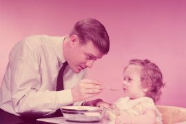 UNITED STATES - CIRCA 1960s:  Father feeding baby girl, sitting in high chair. (Photo by H. Armstrong Roberts/Retrofile/Getty Images)